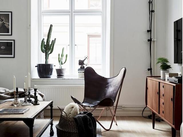 白色的墻面占據大部分室內面積,所以需要為室內增加溫馨感覺來驅散冰冷感受。這是一個只有六十一平米的公寓,設計師利用深棕色提升空間的溫度,帶來不同的感受一起來看看吧。 01、客廳當中白色的長沙發搭配了皮質的休閑椅,棕色的實木家具、沙發上的棕色蓋毯都為空間帶來了非常溫暖親切的氛圍。  02、窗戶沒有窗簾,窗臺上擺放的多肉植物讓室內變得清新自然;實木材質的地板和帶有金屬框架的實木茶幾都是這種色彩的重復使用,讓空間輕松休閑。  03、墻面上設計一個固定的金屬鐵藝的收納架,墻面上一面圓形的無框鏡子帶來精致的感受。這里